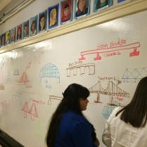 Students use the whiteboard walls to draw different bridge types!